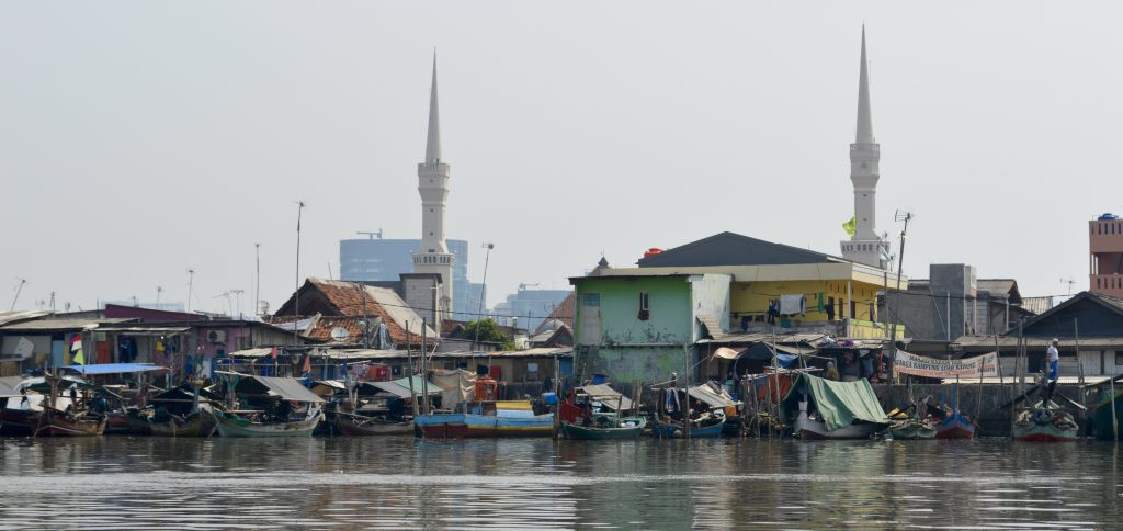 """Remnants of a shanty town near to Sunda Kelapa Harbor - those are being torn down & replaced by concrete nightmare towers. Long term vision is a nightmarish replica of Singapore. """"Progress."""" Minarets of a mosque are also visible (June 2016)."""